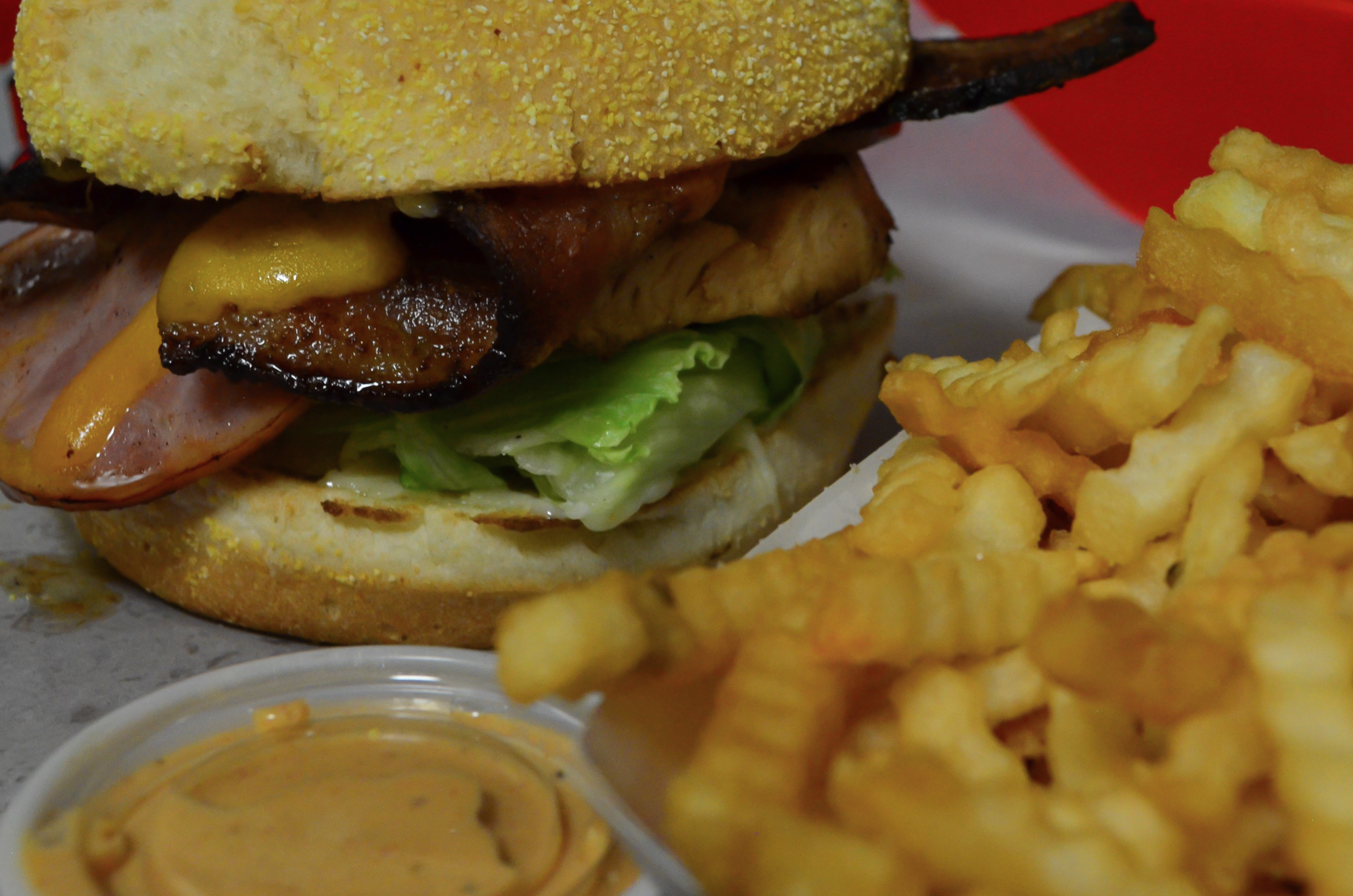 Closeup of the Chicken Club. Grilled chicken breast topped with bacon, ham, Swiss cheese, lettuce, tomato, and mayo. Served with a side of french fries.