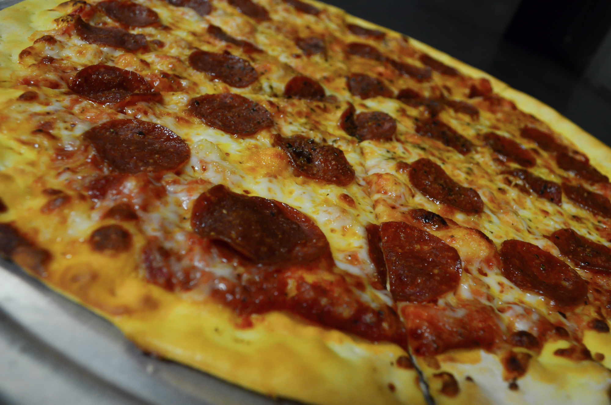 Closeup of a whole pepperoni pizza pie.