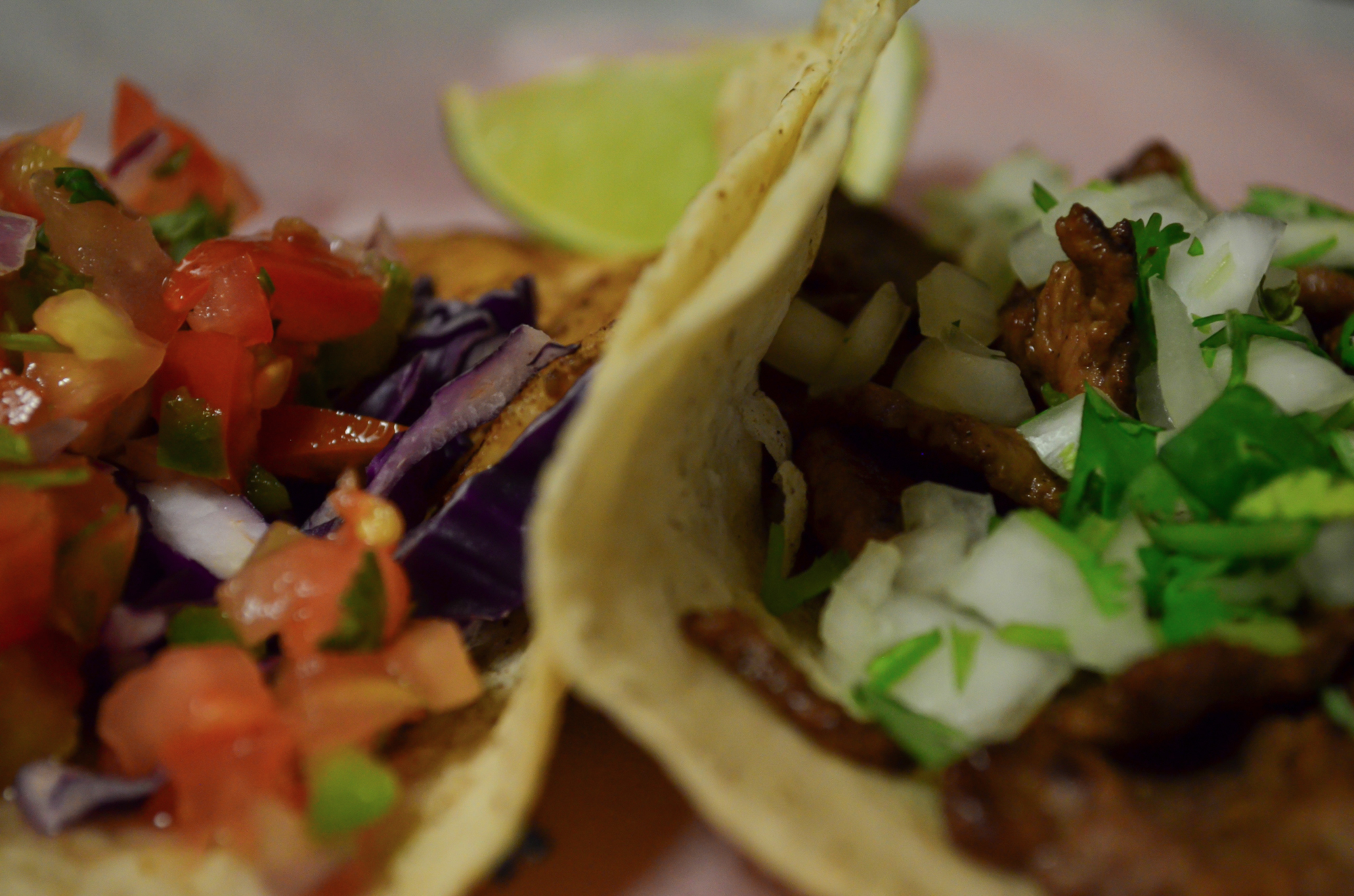 Closeup of two different tacos with a lime wedge in the background.
