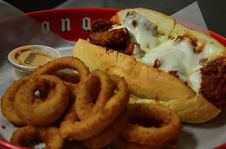 Chicken parmesan hero served with a side of onion rings,
