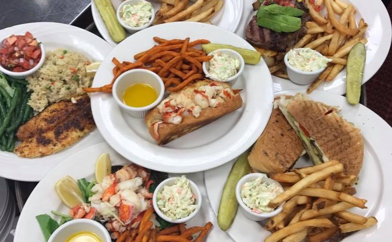 Assorted plates with sweet potato fries, coleslaw, lobster roll, club sandwich and steak