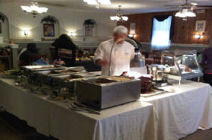 Chef behind a table with multiple different foods