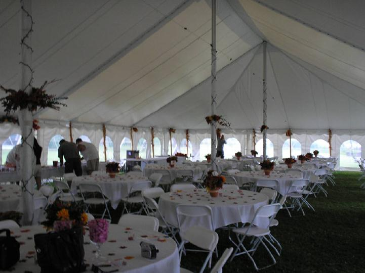 Party event tent with many tables and chairs