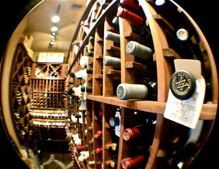 Wine Cellar with a plethora of wines on a wooden cabinet