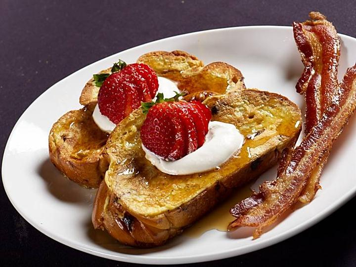 French toast topped with whipped cream, syrup, and sliced strawberries. Served with a side of bacon