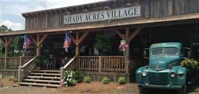 Shady Acres Village front entrance with sign, shrubbery, and American flag