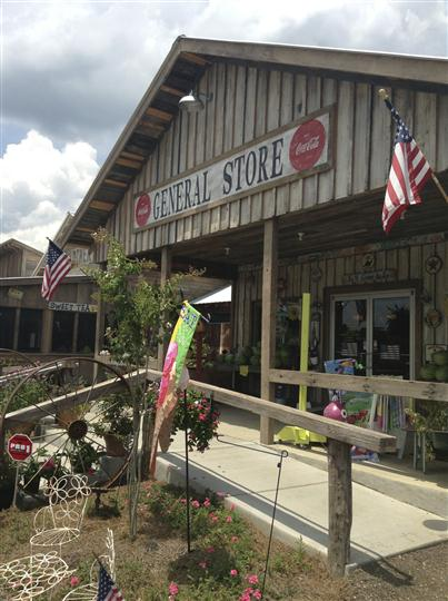 General store front entrance with lawn decorations and 2 American flags