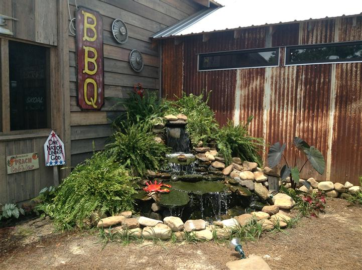 Outdoor pond decoration with BBQ sign in the background