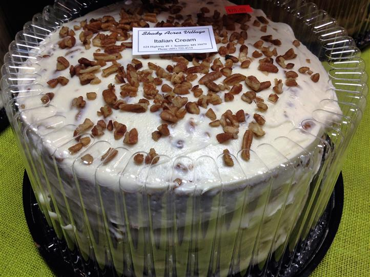 Italian Cream cake in plastic casing with toppings on it