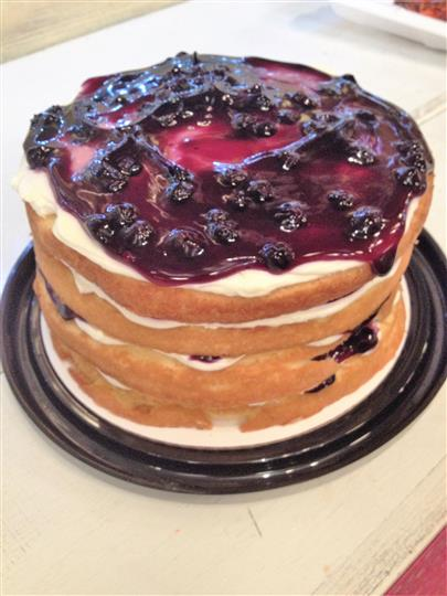 Layered cake with icing and black berry jam topping