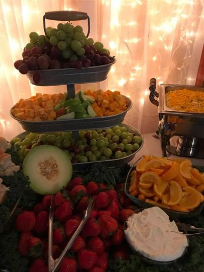 Assortment of a plethora of fruits on a table with a arranged display with a light decoration with curtains