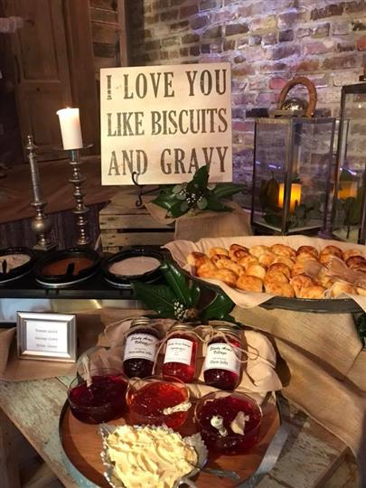 "Sign that reads ""I love you like biscuits and gravy"" with biscuits and jam under it"