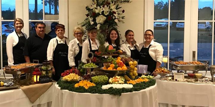Group photo of caterers standing behind an assortment of fruits on a table