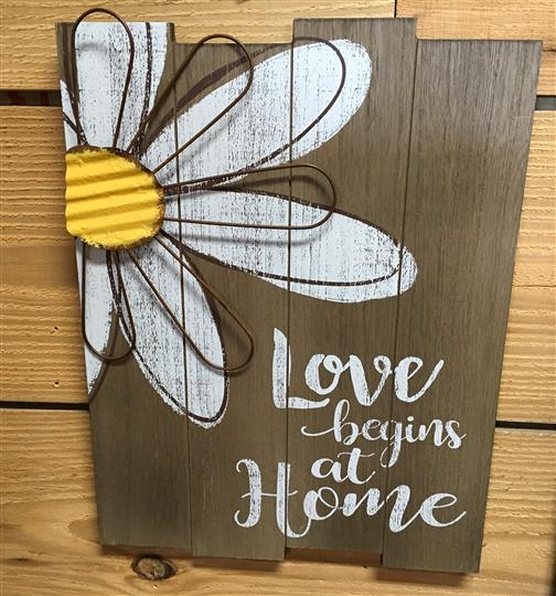 "Sign with a flower and a wooden backdrop that reads ""Love begins at home"""