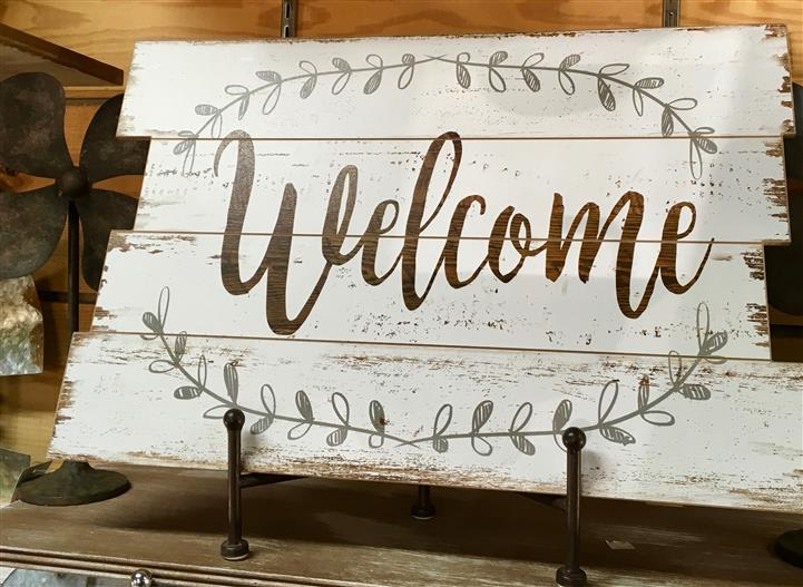 "Sign that reads 'Welcome"" on a white wooden backdrop"