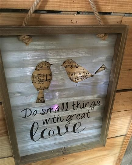 "Sign that says ""Do small things with great love"" with a cut out of two birds"