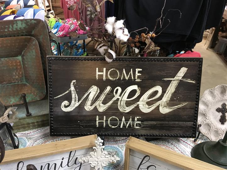 "Sign the reads ""Home Sweet Home"" on a wooden backdrop"