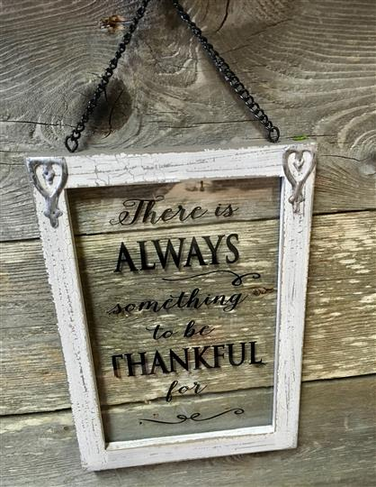"Sign that reads ""There is always something to be thankful for"" with a wooden background"
