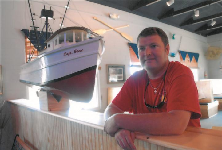 customer smiling for the camera in front of a miniature boat hanging from the ceiling