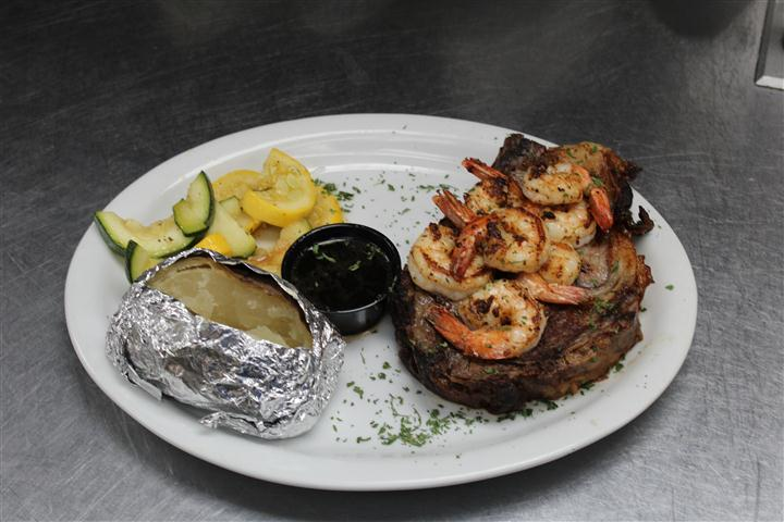 steak topped with cooked shrimp with a baked potato and vegetables