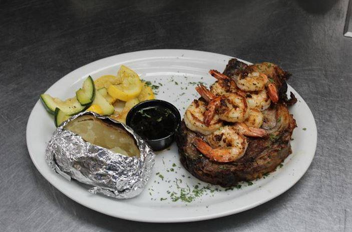 grilled steak on a plate with grilled shrimp and a side baked potato and steamed vegetables