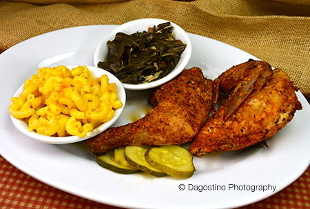A plate of two chicken wings and collard greens a side of mac and cheese and a side of collard greens