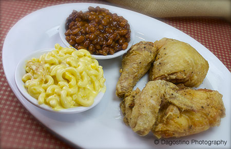 A plate of chicken wings and legs with a side of mac and cheese and baked beans