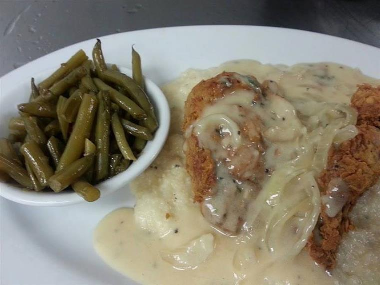 country fried steak covered in gravy with a side of green beans