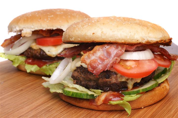 Two hamburgers with lettuce, tomato, bacon, onion and pickles on a bun