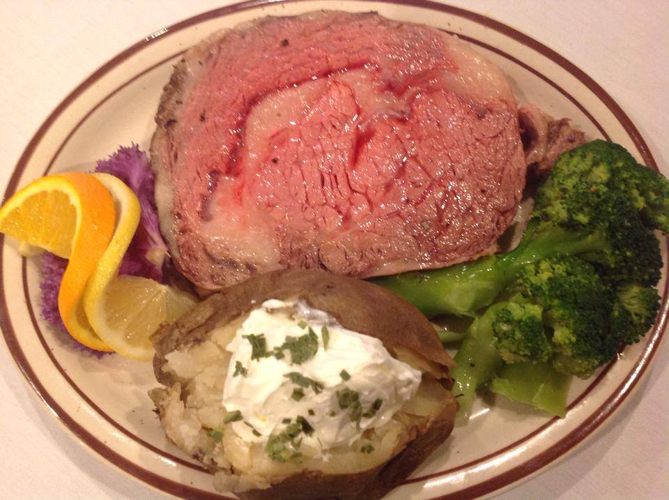 roast prime rib with baked potato and broccoli
