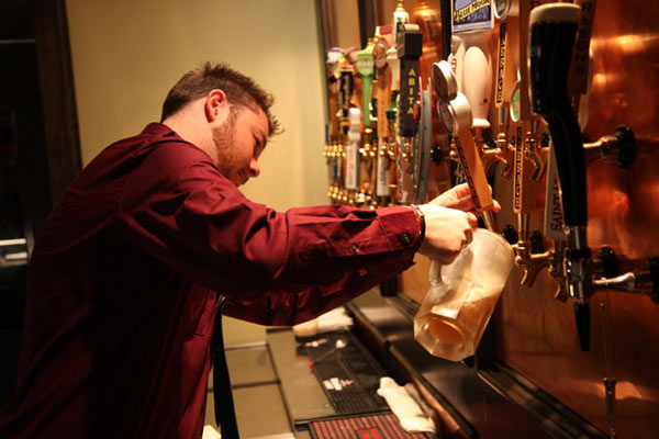 male getting beer from a tap