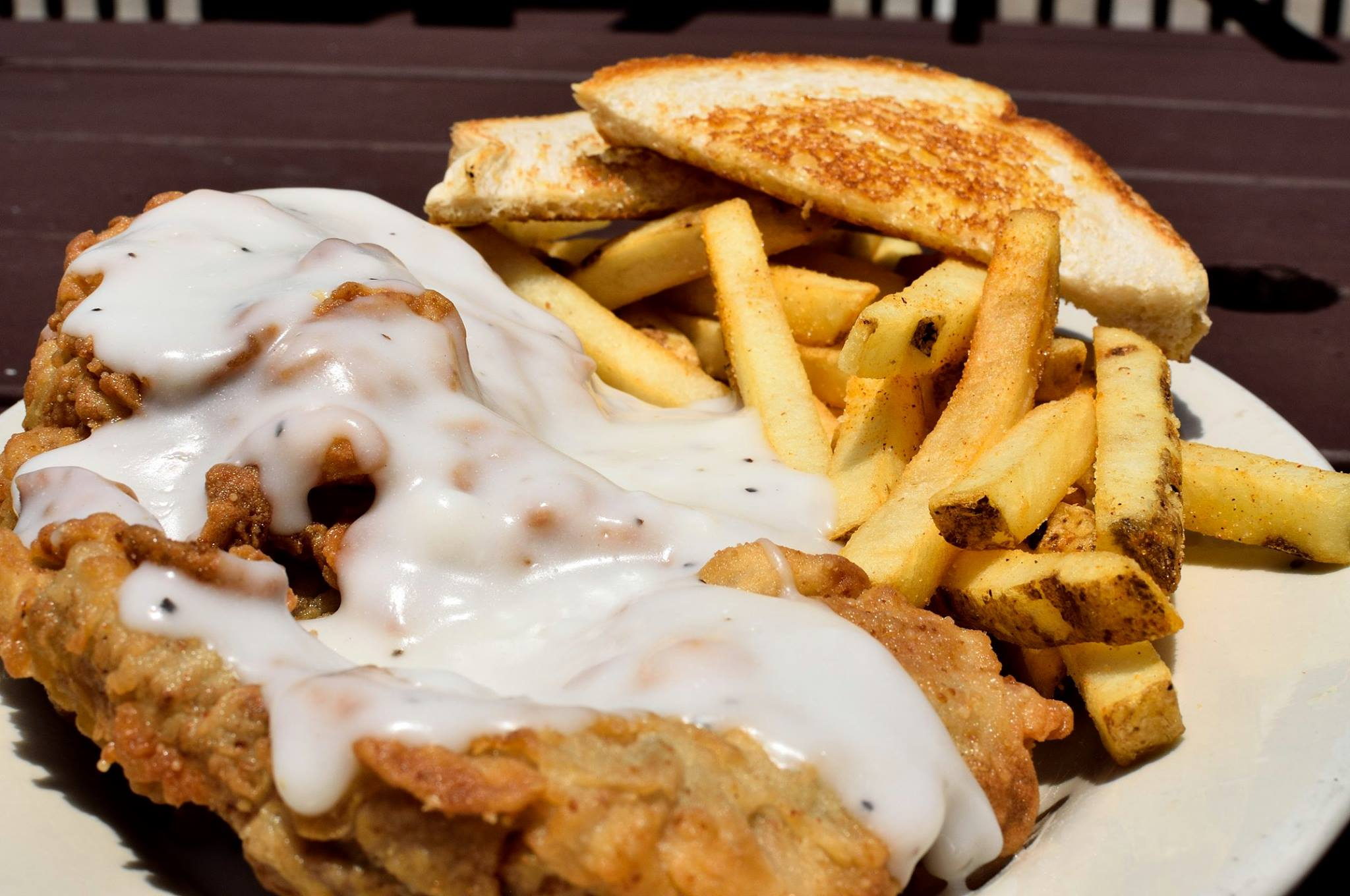 country fried steak topped with gravy, a side of french fries and toast