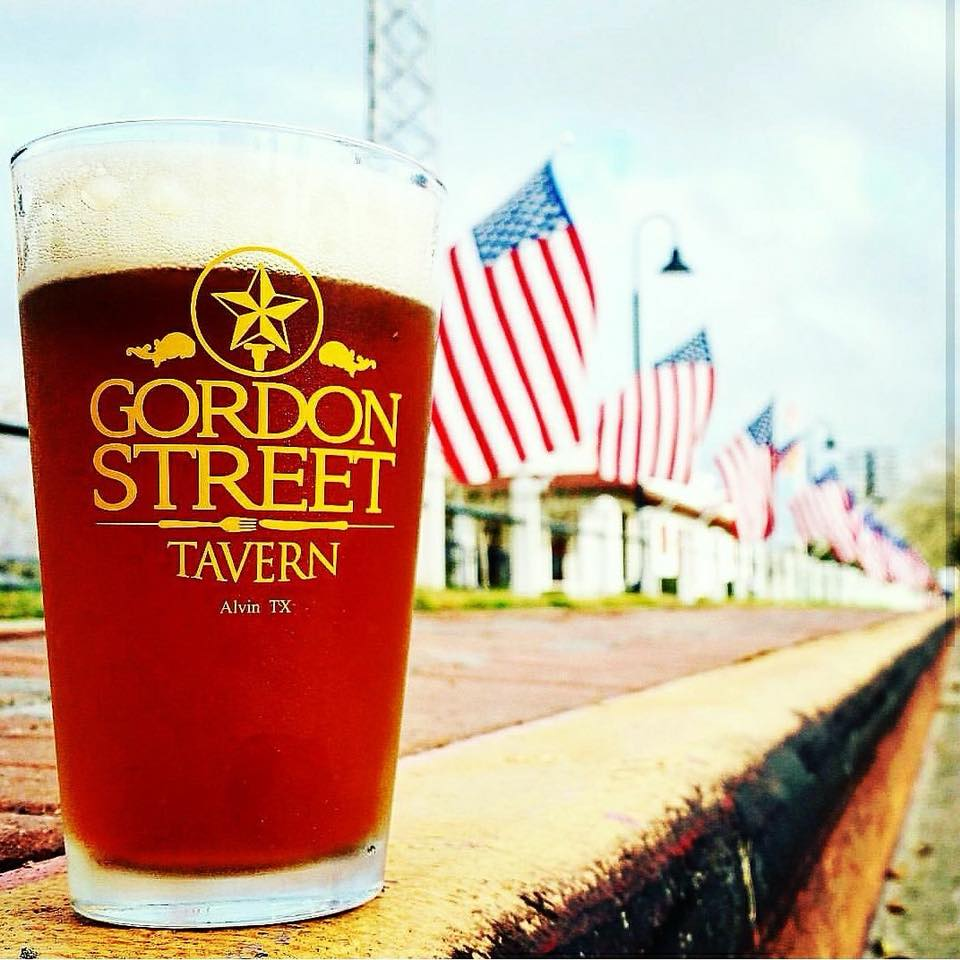 glass of beer with gordon street tavern on it with american flags in the background