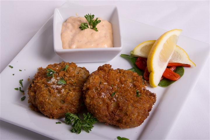 two crab cakes with dipping sauce