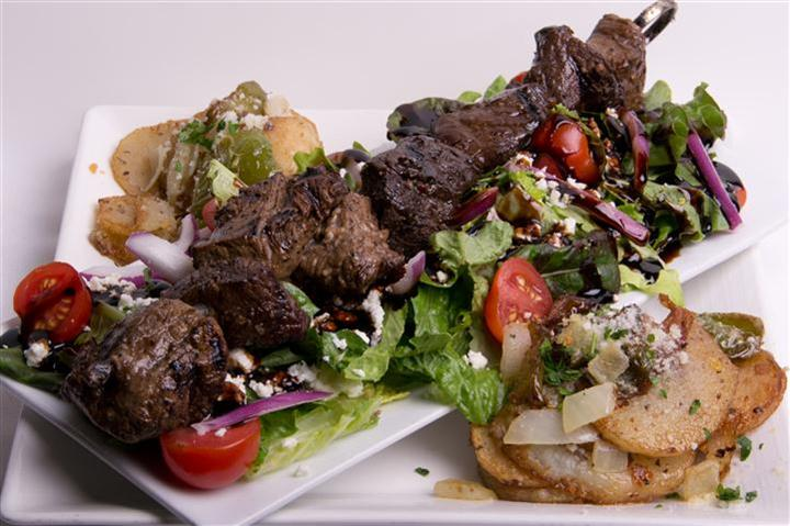 steak skewers over a bed of salad