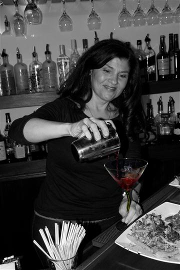 bartender behind the bar making a mixed cocktail