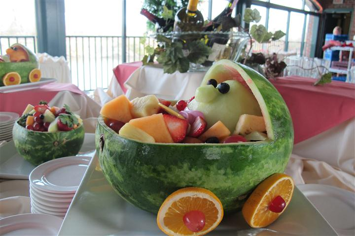 table display of a fruit basket filled with smaller fruit