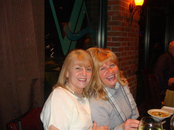 two woman enjoying themselves at the restaurant laughing at the camera