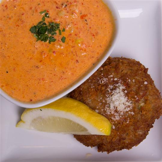 crab cake with lemon wedge and dipping sauce