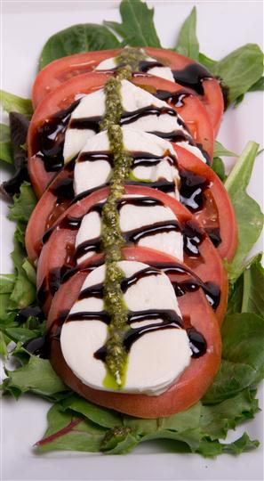 caprese salad over a bed of spinach