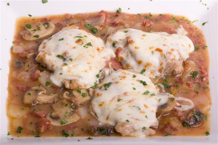 three chicken cutlets with cheese and mushroom sauce