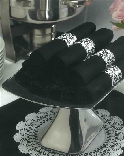 Cutlery wrapped in black napkins on pedestal on doily