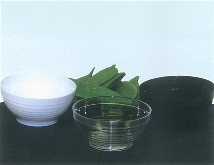 Set of clear, black, white bowls with edamame on black tablecloth