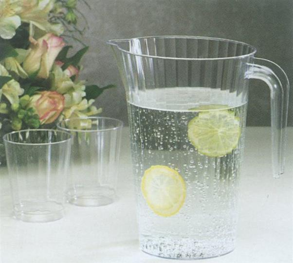 Crystal pitcher with lemon water next to two empty tumblers