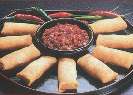 Cocktail spring rolls with peppers and dip on black tray