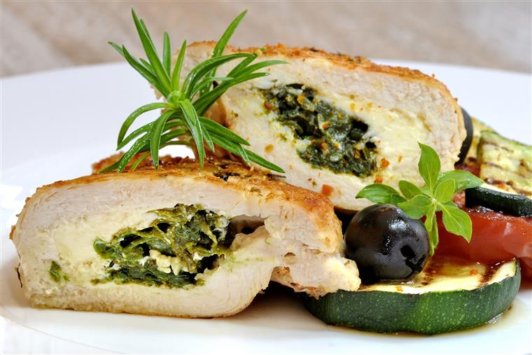 Chicken stuffed with spinach atop zucchini, tomato, black olives