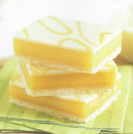 Lemon bars stacked on green napkins