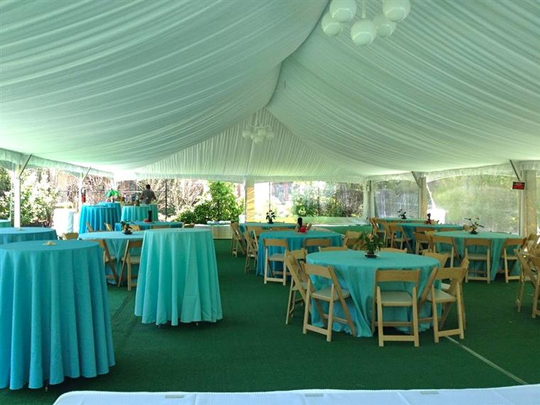 Tables with turquoise cloths inside of white tent
