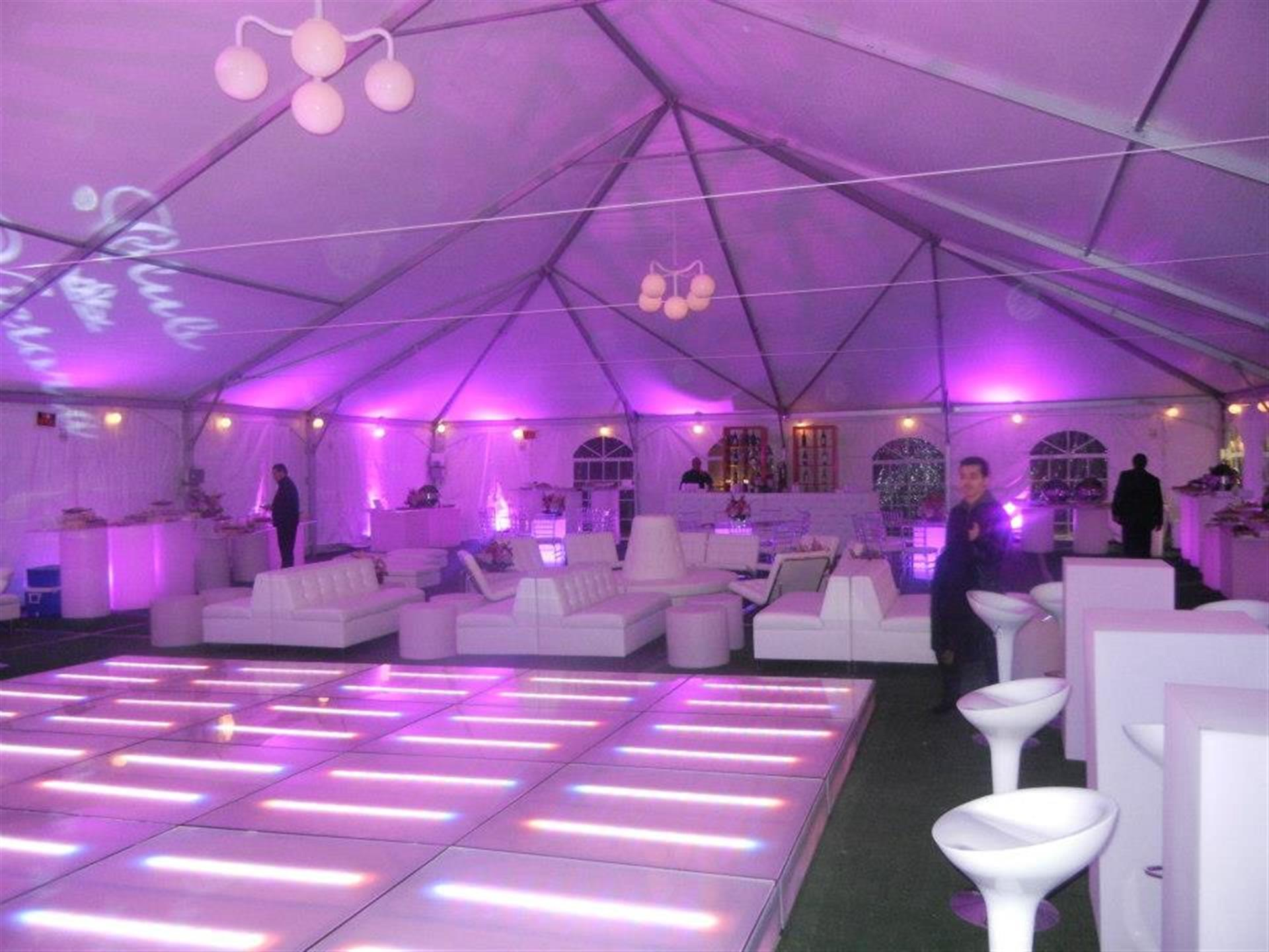 Dance floor and seating under purple-lit tent