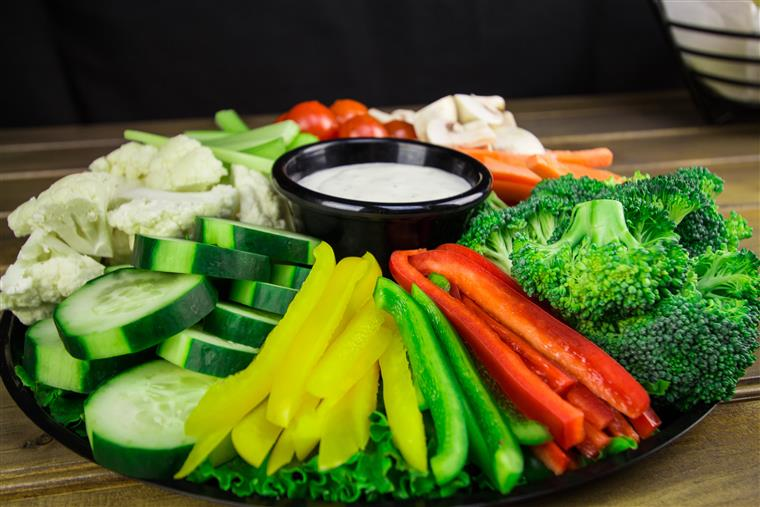 Vegetable platter of cucumbers cauliflower, peppers, carrots, tomatoes, broccoli on black plate